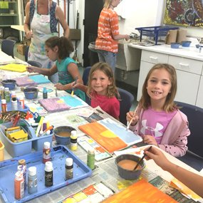 two caucasian girls smiling while in art class