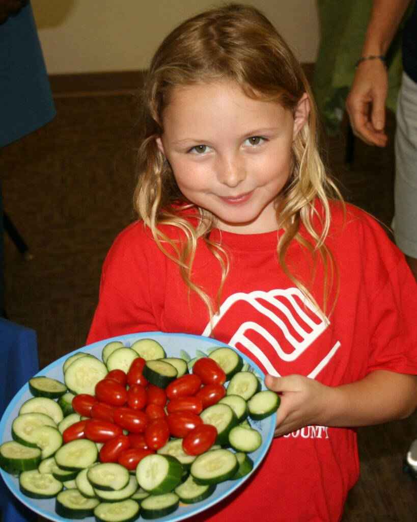 young girl in red shirt smiling and holding a tray of cucumbers and tomatoes
