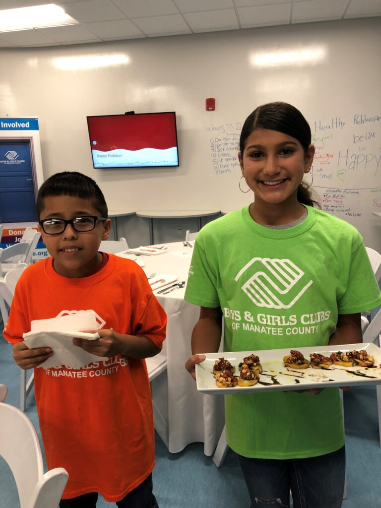 young boy in orange shirt with a girl in a green shirt holding a tray of appetizers