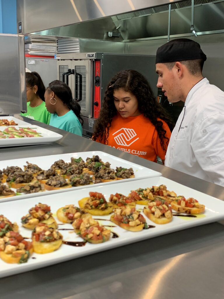 three young girls with chef in kitchen