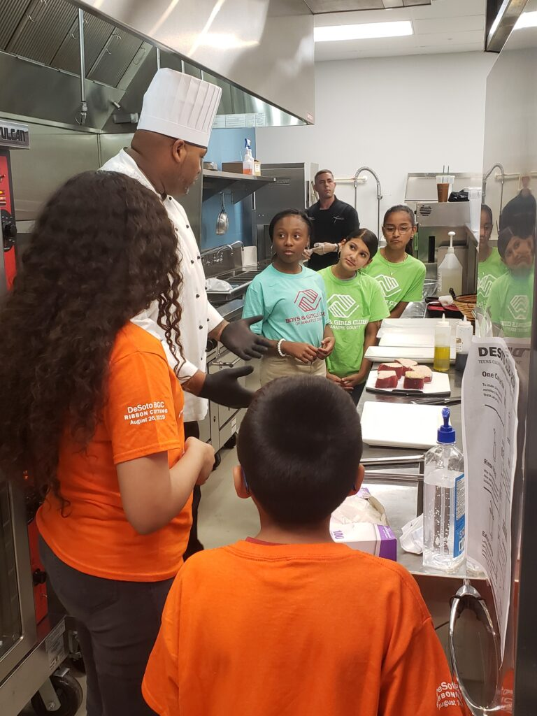 chef with group of young students in kitchen
